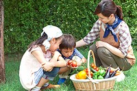 Children with mother looking at vegetables in basket