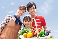Portrait of family holding basket filled with fresh vegetables