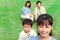Portrait of family on lawn, smiling, differential focus