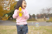 Young girl playing with a bubble blowing toy