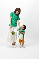 Mother and son holding shopping bags of groceries