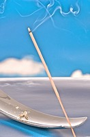 Incense stick burning on a background of  blue sky and white clouds