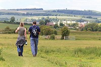 couple walking away along a path in a field