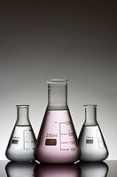 three laboratory flasks with liquid and a white background