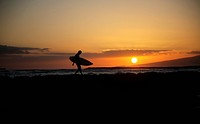 Hawaii, Oahu, Waikiki, Silhouette of a surfer walking on a rock wall at sunset