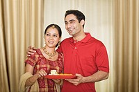 Couple holding a plate of sweets and smiling