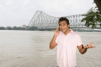 Man talking on a mobile phone with a bridge in the background, Howrah Bridge, Hooghly River, Kolkata, West Bengal, India