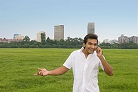 Man talking on a mobile phone in a park, Kolkata, West Bengal, India