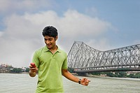 Man text messaging on a mobile phone with a bridge in the background, Howrah Bridge, Hooghly River, Kolkata, West Bengal, India
