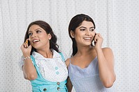 Two women talking on mobile phones and smiling
