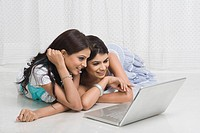 Two women using a laptop and smiling
