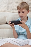Boys sits cross_legged with portable games console