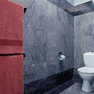 White toilet in bathroom recess with grey granite wall tiles