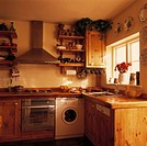 Stainless steel oven and white washing machine below extractor in small wood kitchen with fitted dishwasher