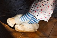 A woman wearing fur-lined moccasin slippers, candy striped socks and polka dot pyjamas with her feet in the sun