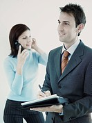 Businessman holding a personal organizer with a businesswoman talking on a mobile phone behind him