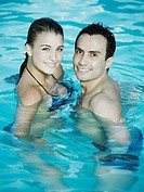 Portrait of a young couple standing in the swimming pool