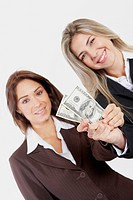 Portrait of two businesswomen holding American paper currency