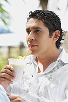 Close_up of a mid adult man drinking a glass of juice