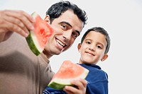Low angle view of a mid adult man carrying his son and holding watermelon slices