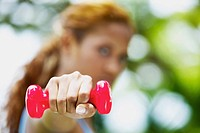 Close_up of a young woman holding a dumbbell