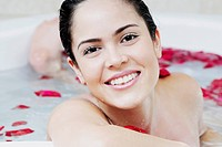 Portrait of a young woman in a bathtub and smiling