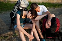 A backpacker couple waiting on the side of a road