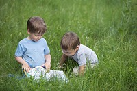 Two boys looking at a book in a field