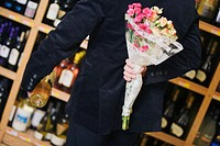Mid section view of a man holding a bouquet of flowers with a wine bottle