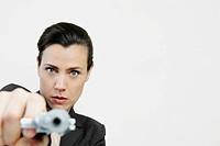 Portrait of a businesswoman pointing a gun
