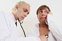 Close_up of a male doctor examining a patient with a stethoscope