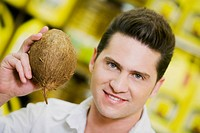 Portrait of a young man holding a coconut