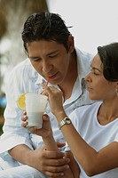 Close_up of a mid adult woman feeding a glass of juice to a mid adult man