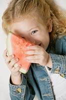 Portrait of a girl smiling and holding a slice of watermelon