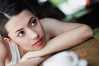 Close_up of a young woman leaning on a table and thinking