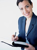 Portrait of a businesswoman smiling and writing on a file