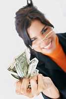 Portrait of a businesswoman crushing American dollar bills