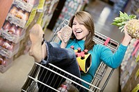 Young woman sitting in a shopping cart and laughing