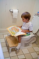 book kid young boy sits potty reading magazine