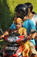 Ubud (Bali, Indonesia): a family on a scooter, with the boy dressed up in traditional Balinese clothes for a children show