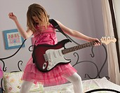 Young girls playing guitar on her bed