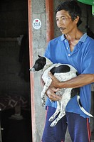 near Ubud (Bali, Indonesia): a farmer receiving a puppy as gift by the B.A.R.C., a local volunteers association that helps street dogs