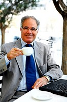 This is a portrait of an older business man drinking a cup of coffee while sitting with his laptop in a cafe