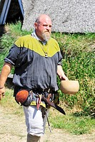Man in Viking costume carrying water bowl