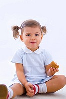 Little girl holding partly eaten muffin
