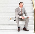 Portrait of a cheerful businessman sitting on steps holding paperwork in his hands
