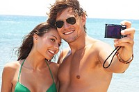 An attractive couple together at the beach, taking a selfportrait