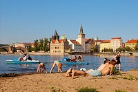 prague - people enjoying summer strelecky island beach - old town in backgroung