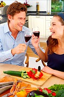 Young couple in their kitchen enjoying a class of wine