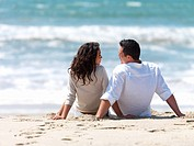 Young couple sitting together on beach